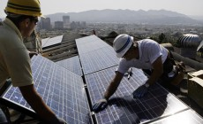 Team leader Edward Boghosian, right, and electrician Patrick Aziz, both employees of California Green Design, install solar electrical panels on the roof of a home in Glendale, Calif., Tuesday, March 23, 2010.  (AP Photo/Reed Saxon)